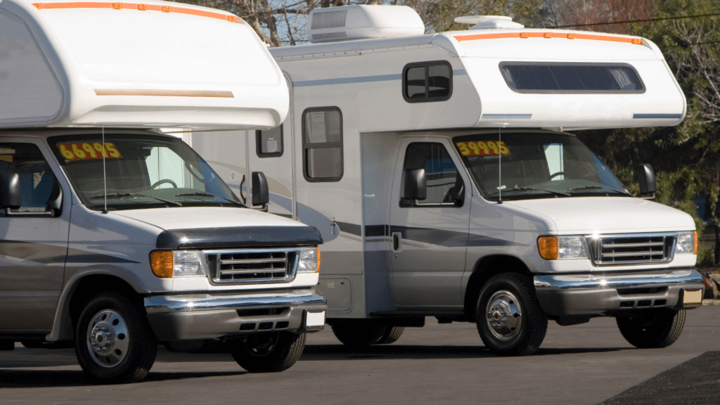 Class C motorhomes on RV lot with prices on their window.
