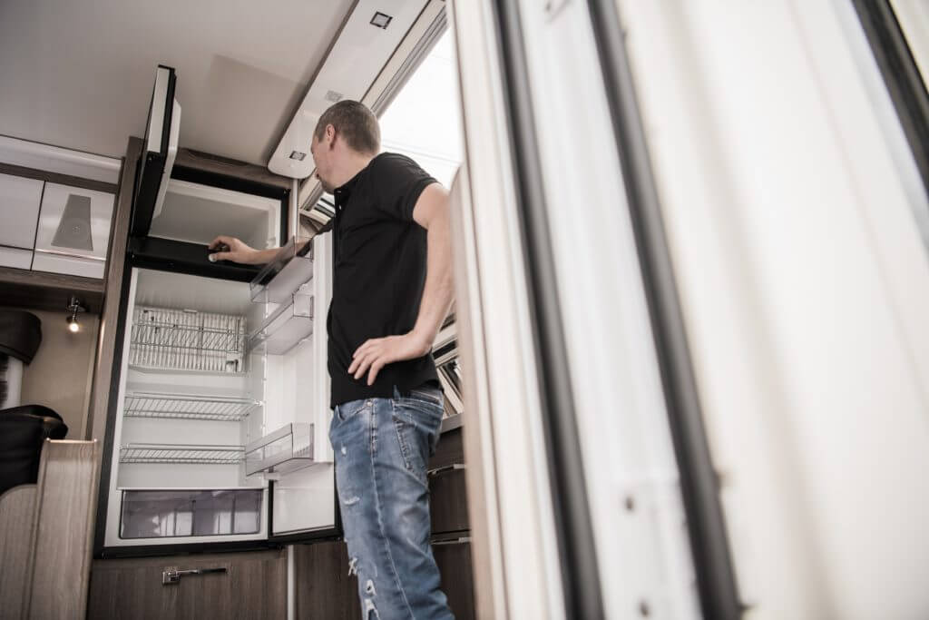 Man standing in front of an open fridge, looking in the freezer trying to troubleshoot RV refrigerator repair