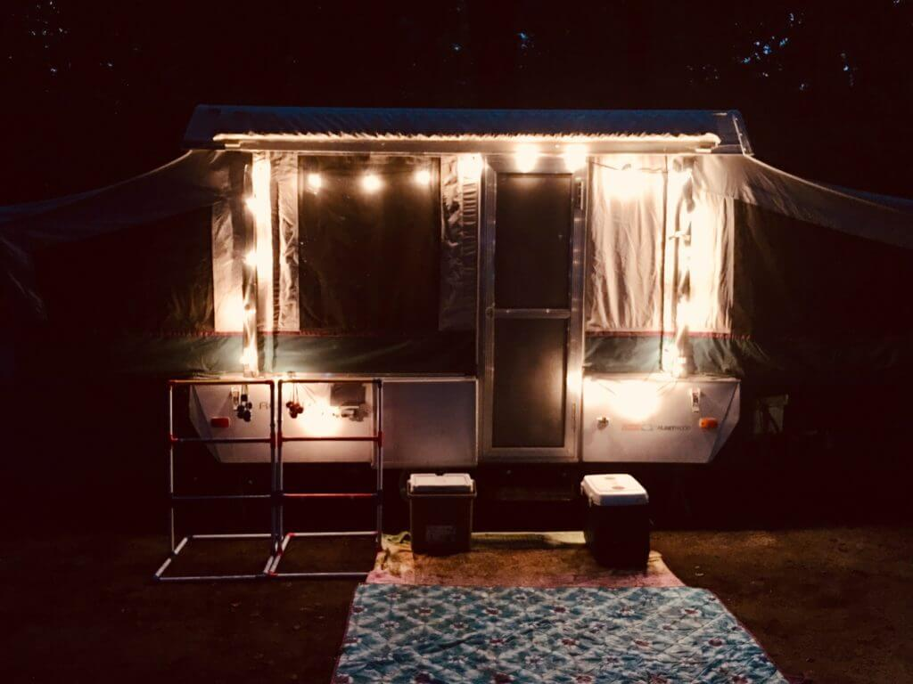Small camper with bathrooms at night with string lights outside