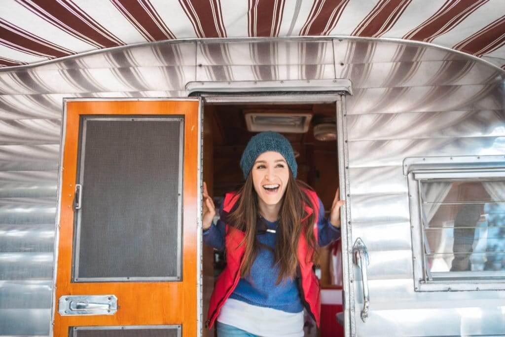 Woman sticking her head out of the door of a small camper with bathrooms