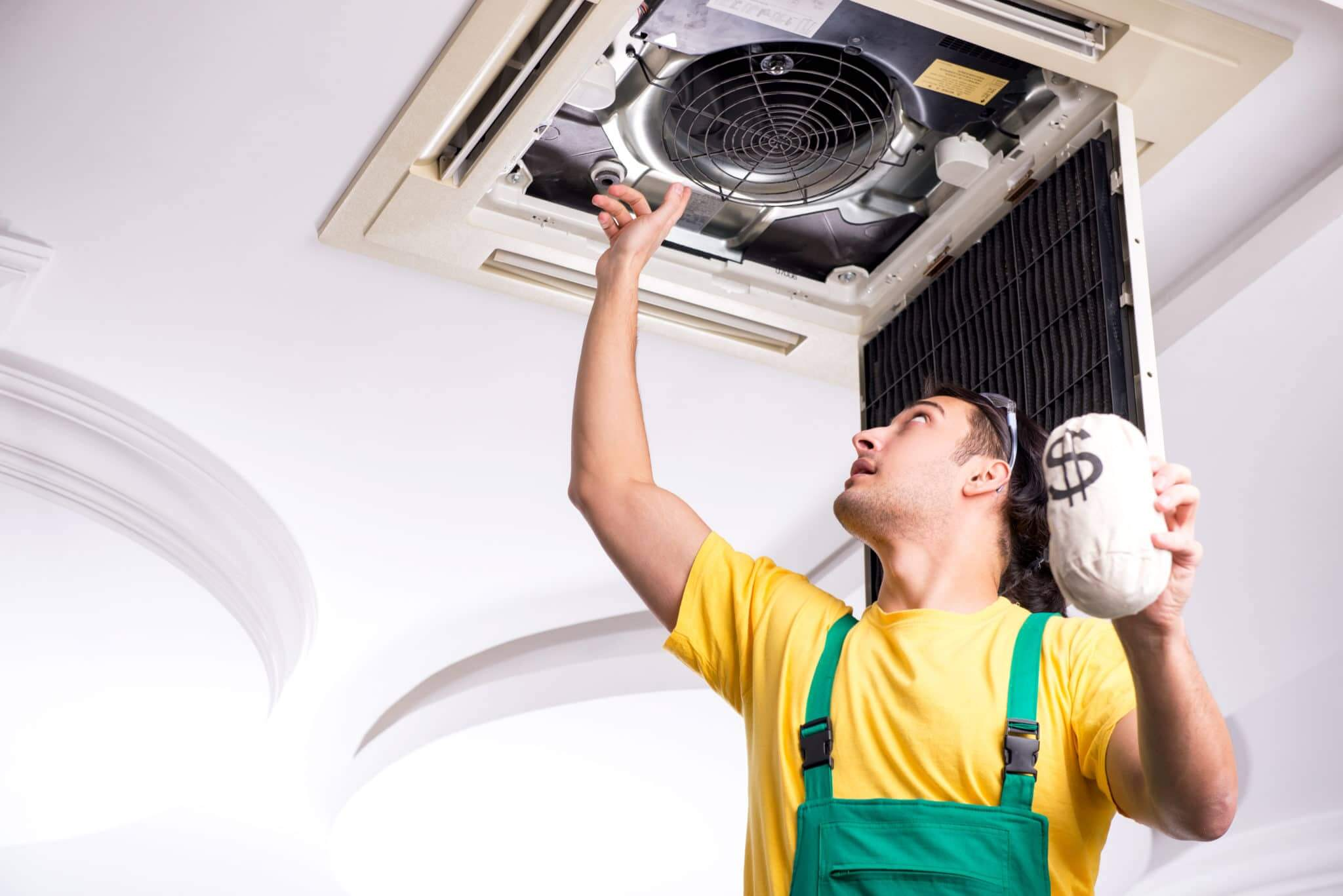 The young repairman repairing ceiling air conditioning unit