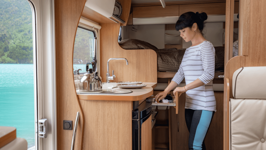Inside the RV kitchen a woman is putting things away in a drawer knowing space is an important consideration in making an RV purchase.
