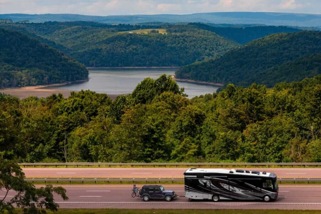 A Class A motorhome, towing a jeep, is rolling down the highway beside a lake and mountains.