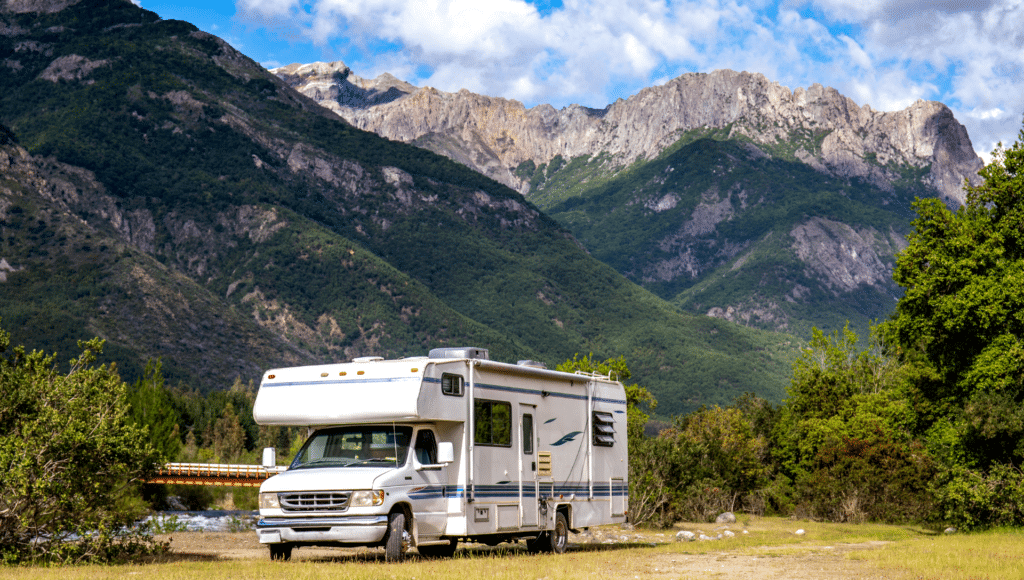 A Class C motorhome sits amongst green trees with mountains in the background underneath a blue sky with white puffy clouds.