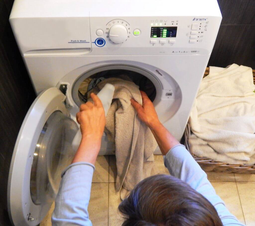 Person adding laundry into a combo washer and dryer which has been recommended as one of the best for RVs