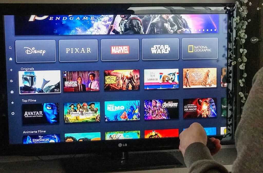 A woman with a remote standing in front of a TV that is showing the different movie choices on Disney Plus. Disney is a great streaming option for watching TV in your RV.