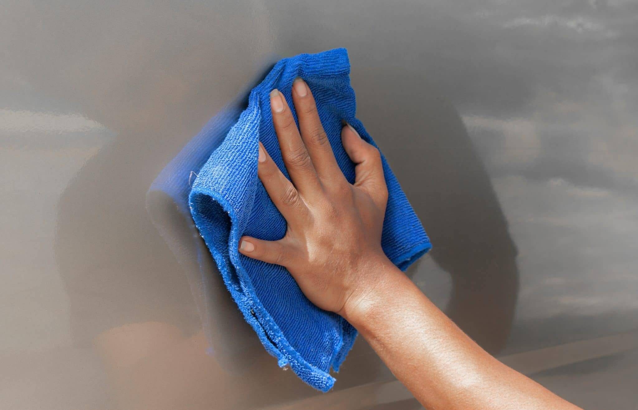 A hand is holding a blue microfiber cloth while waxing an RV with the best RV wash and wax.