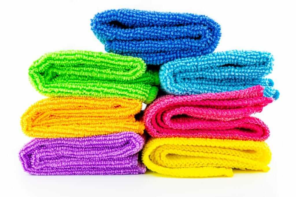 A stack of seven folded microfiber cloths in bright colors.