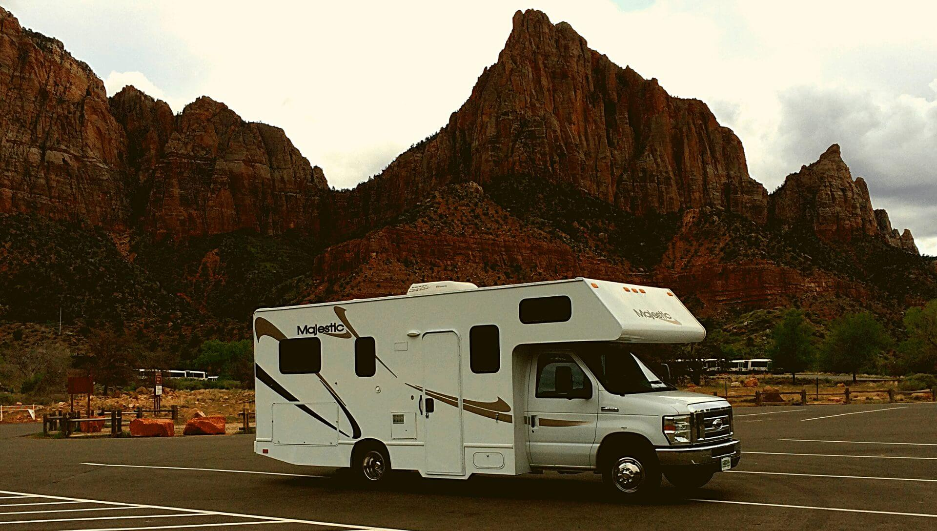 A Class C diesel motorhome is parked at Zion National Park with the mountains behind it.