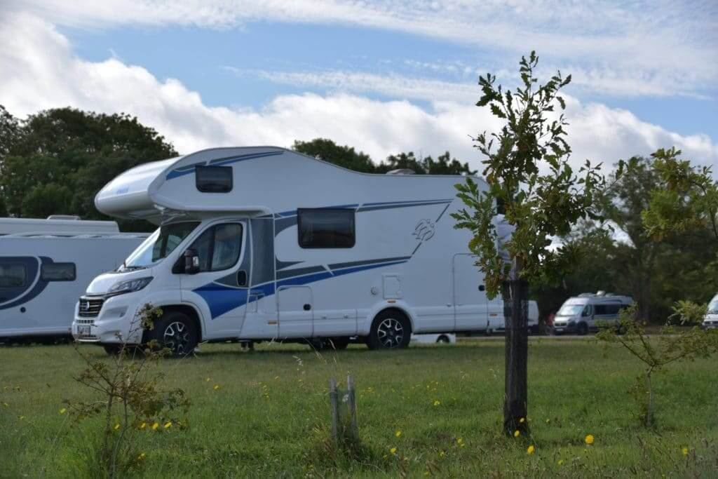 A Class C Diesel Motorhome is parked at a campground next to a tree. A Class B motorhome is parked behind it.