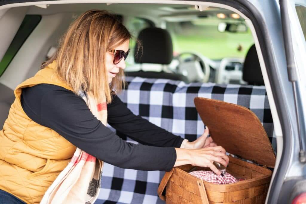 A woman sits in the tailgate area of her SUV with a picnic basket since this is a way to save money on activities while on a roadtrip.
