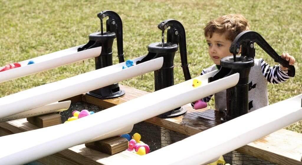 A child is pumping water to race rubber ducks down a tube on a local farm.