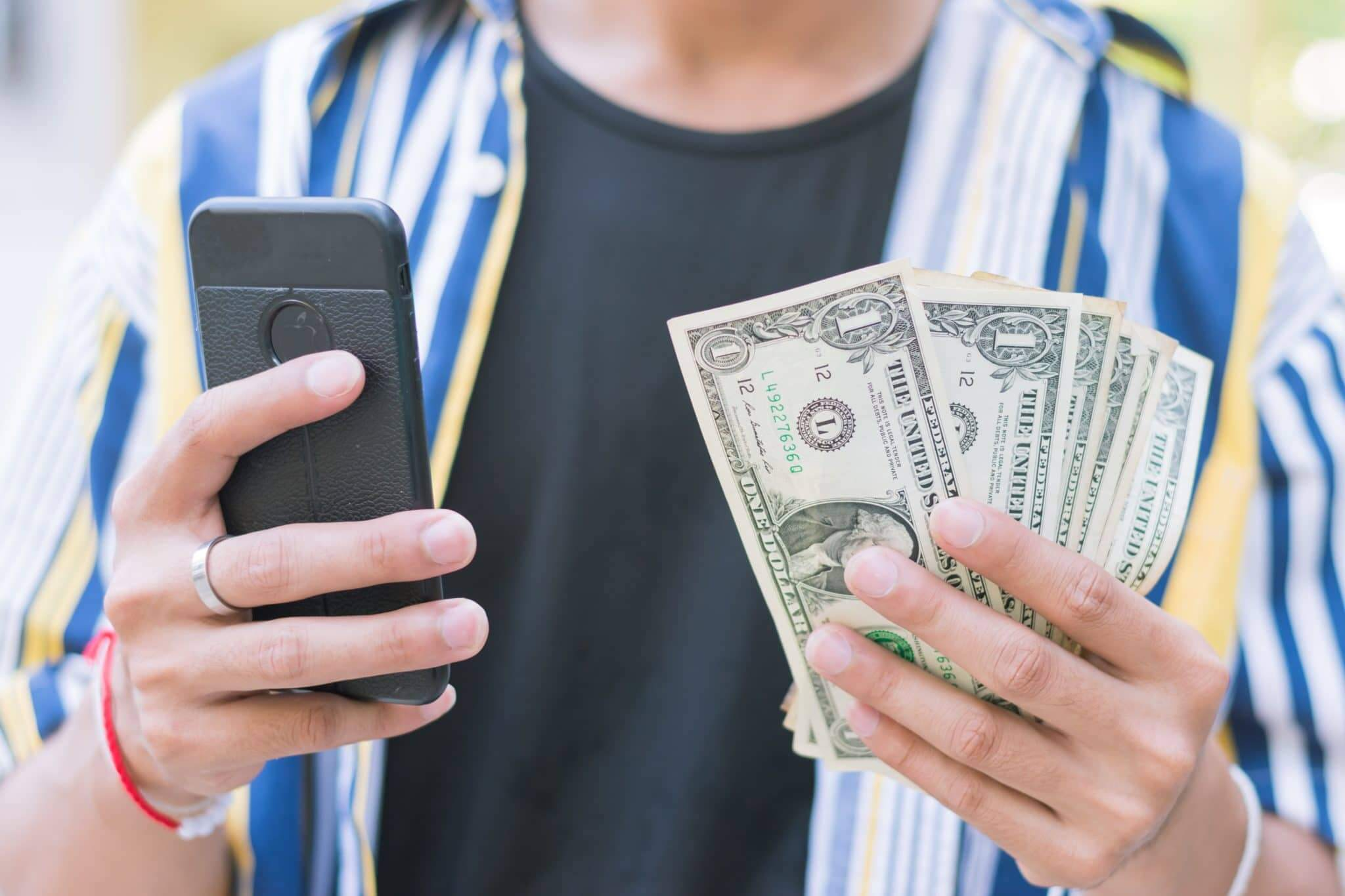 A walking man holding cash in one hand and looking at a cell phone in the other.