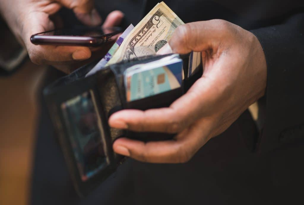 A man holding his open wallet with cash and credit cards while looking at his phone for apps to help you save money