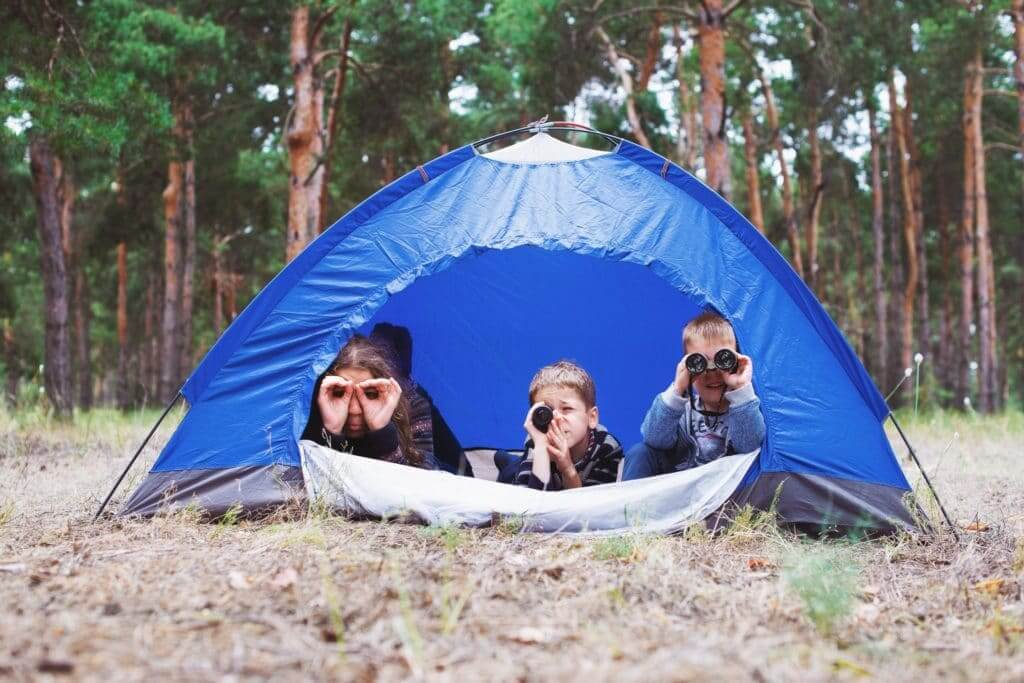 Kids sitting in tent while camping looking at nature with binoculars