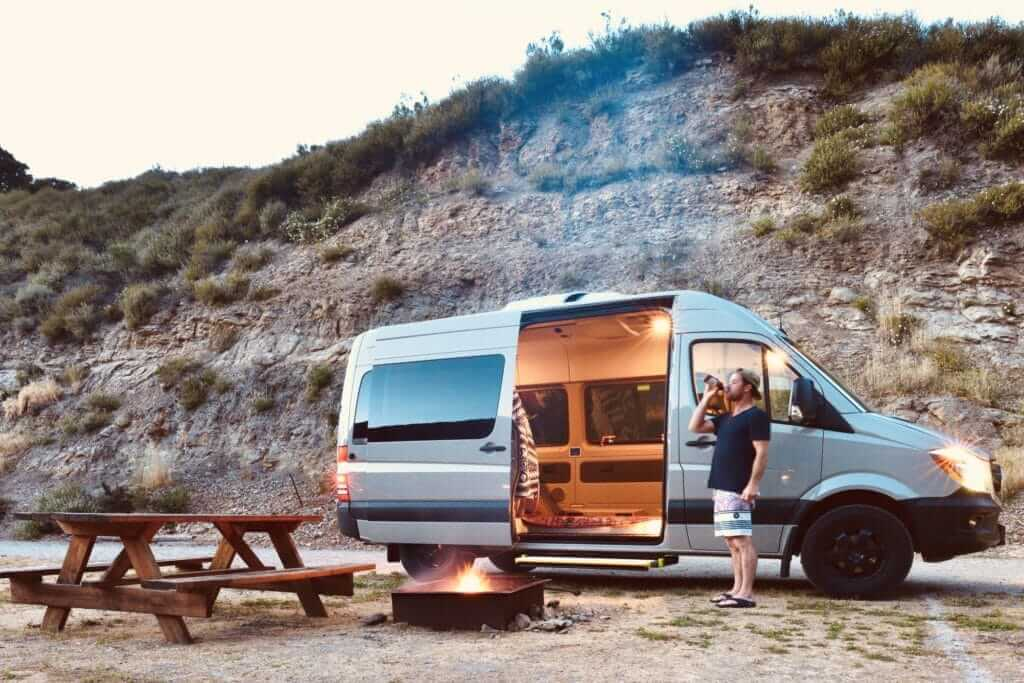 Man drinking in front of his small RV on a beach