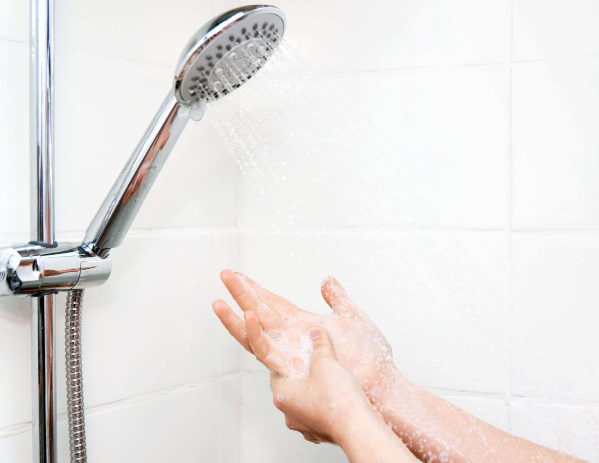 Women washing hands in water from RV shower head