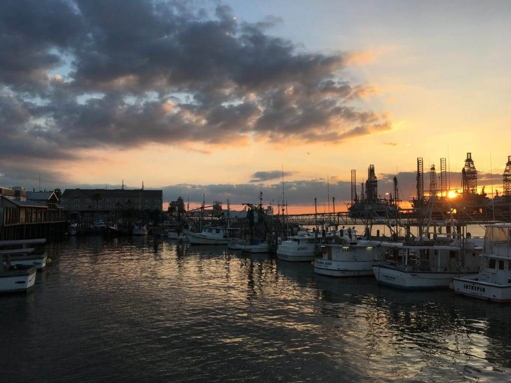 Boats in a marina with the sun setting in the background. The Gulf Coast is a great place to visit when staying at Thousand Trails Texas parks.