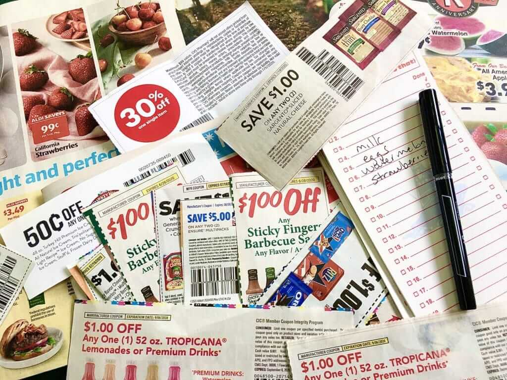 PIle on coupons with a grocery list. A great tip for how to save money on food is to use coupons when you can.