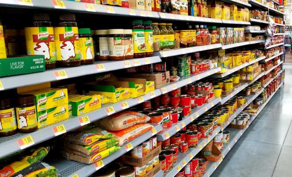 A grocery store isle with canned food on the shelves. A great tip for how to save money on food is to buy canned food as it's cheaper and lasts longer.