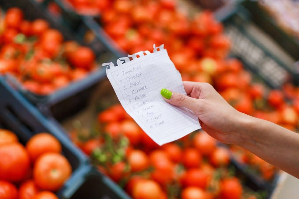 Woman with green nail polish holding a grocery list with tomatoes in the background. A great tip for how to save money on food is to plan ahead with a list so you don't over buy.