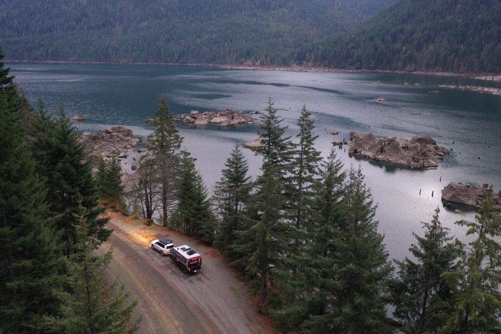 Aerial shot of an SUV towing a travel trailer down a dirt road next to trees and a river. You can  make money renting your RV to adventurous folks like this.