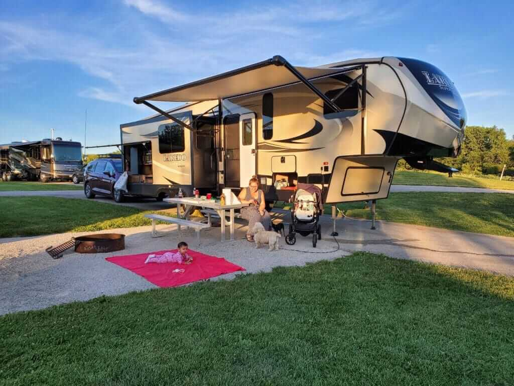 A woman sitting outside a fifth wheel with a baby on a blanket and a small dog. You can  make money renting your RV to families like this.