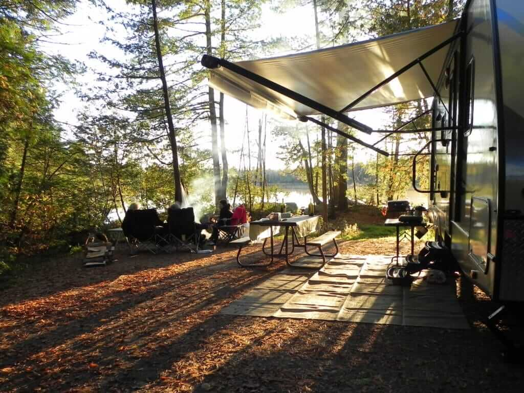 RV awning covering sitting area on wooded campsite