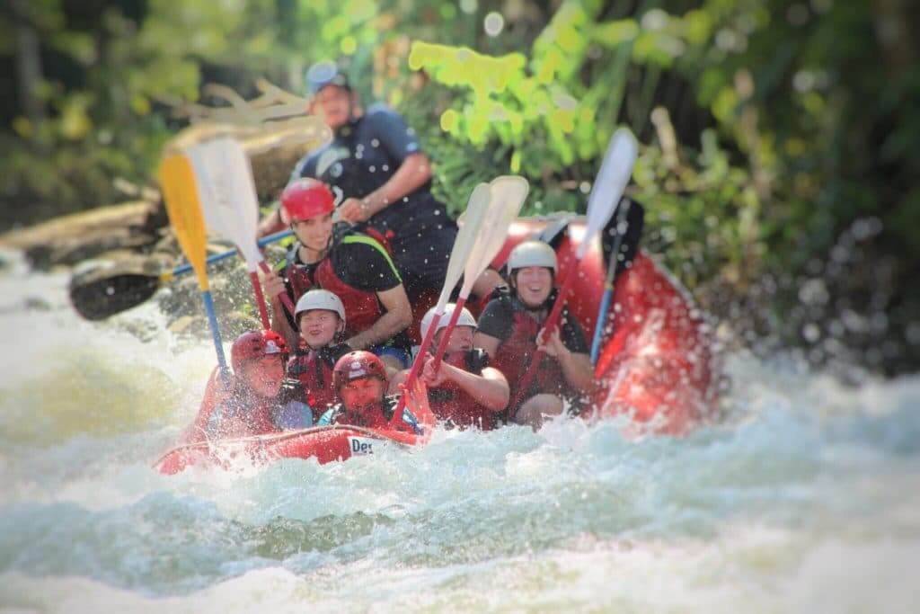 People smiling going down a rapid in a red raft. Go white water rafting when you are staying at Thousand Trails Yosemite.