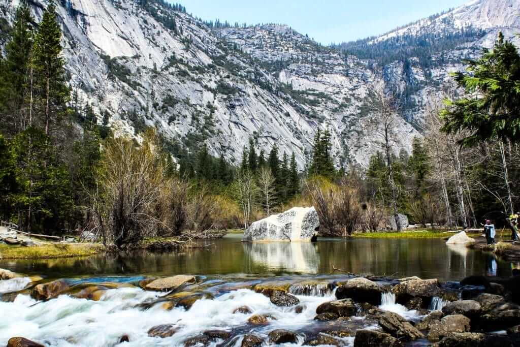 Small river with water flowing over rocks and a snow covered mountain in the background. Yosemite National Park is just 5 miles from Thousand Trails Yosemite.