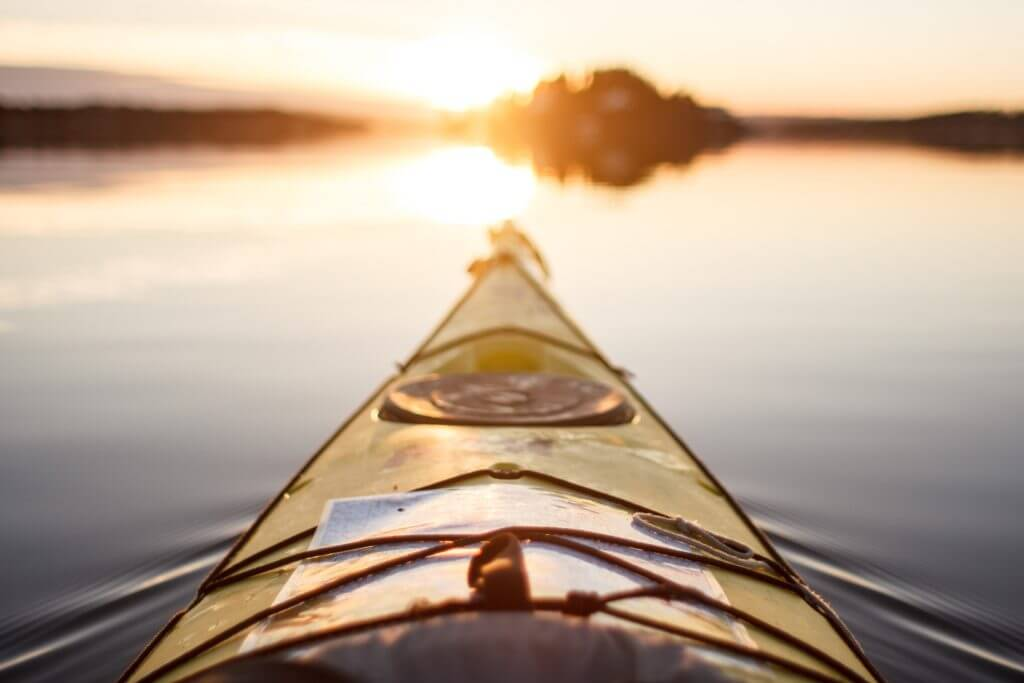 Close up of the front of a kayak on the water with the sun rising. Kayaking is one of the many activities you can partake in when strawberry reservoir camping.