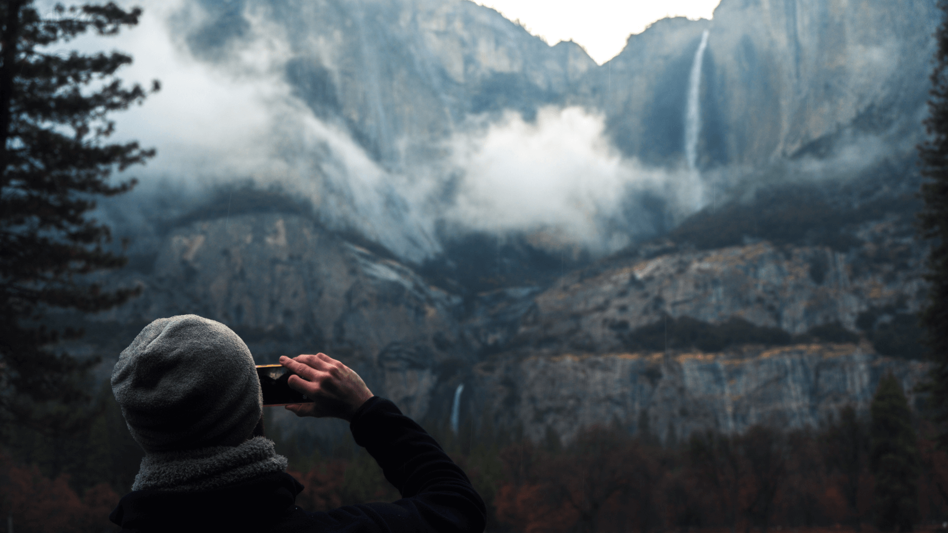 A man with a beanie on films Yosemite falls from his iphone on a cloudy day.
