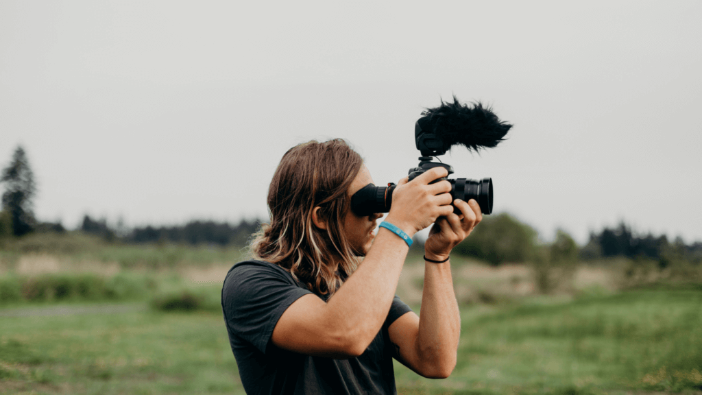 In a grassy field a man with long blond hair films with an slr camera up against his face.