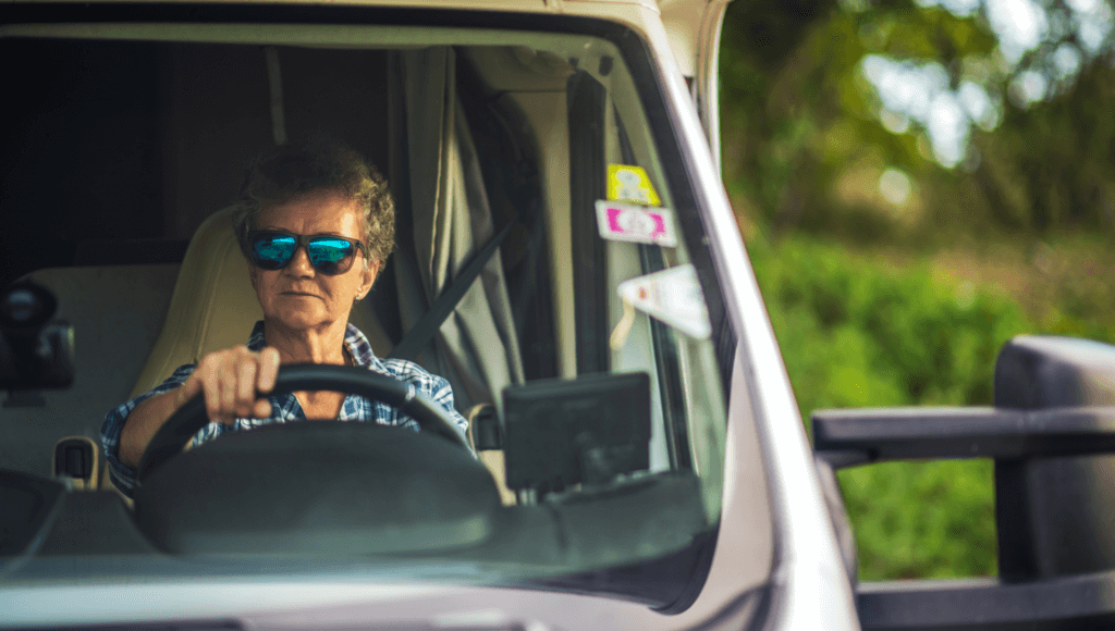 A woman wearing sunglasses sits behind the wheel of her Class C Motorhome.