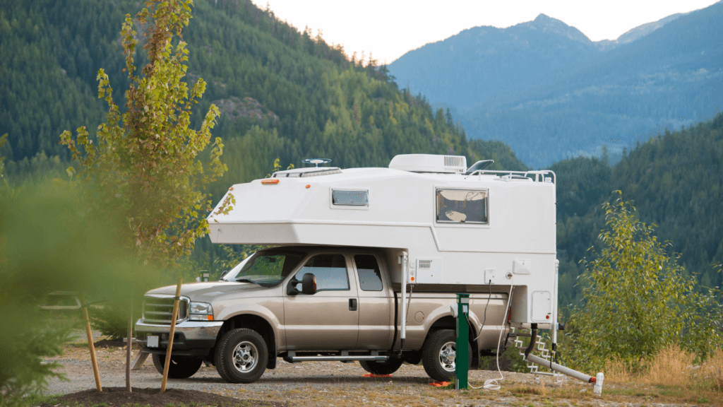 A tan truck with a white RV camper is parked in an RV campground with green mountains in the background.