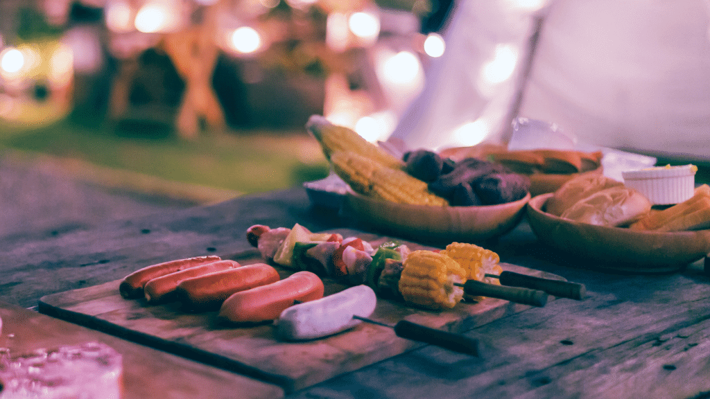 A table has foods for the barbecue laid out ready to be grilled. There are sausages on a skewer and two skewers with veggies. There is a platter with some steaks and bowls with corn, bell peppers, and some breads to get toasted.
