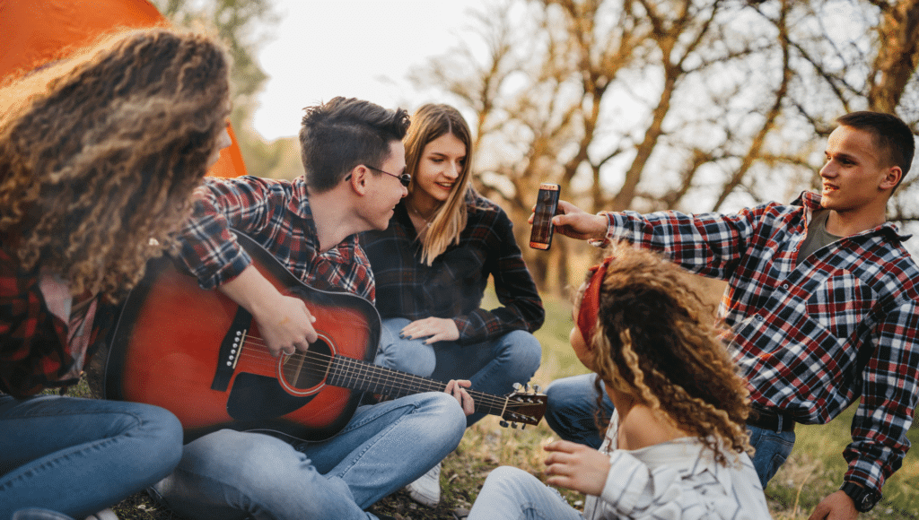 A group of friends are sitting on the ground in front of a tent. One man is holding a phone while another man plays campfire songs on the guitar.