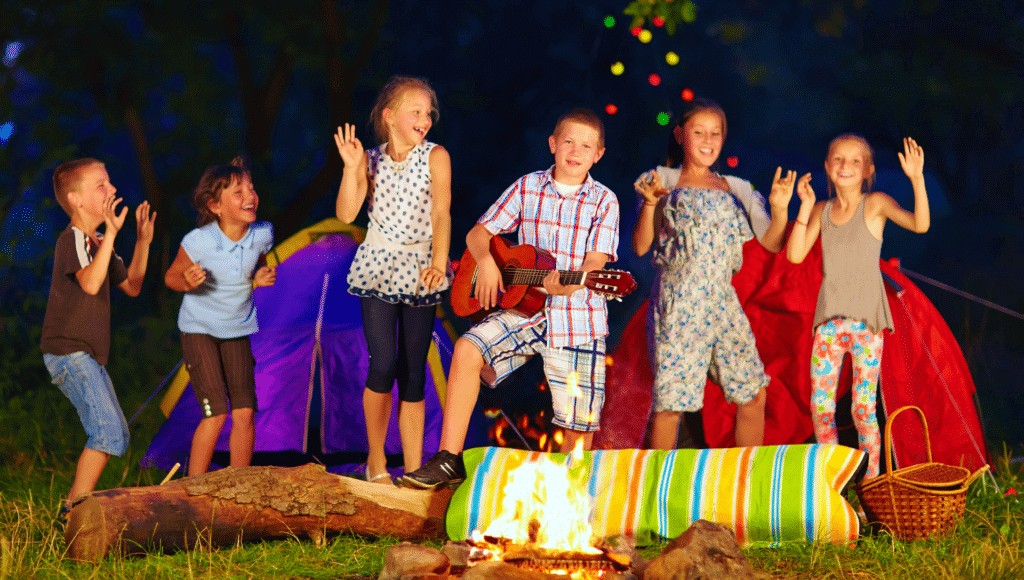 Three young boys and three young girls sing campfire songs in front of a campfire by their tent. One boy is playing the guitar.
