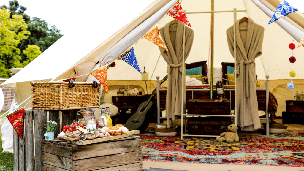 A colorful glamping set up with a rustic brunch set up. Inside the tent are matching robes ready to be worn with a large luxurious bed in the back. There is a colorful rug on the ground and a guitar to be played.