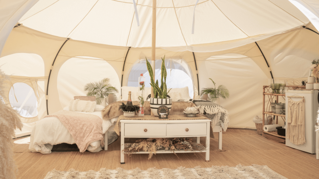 A white yurt glamping tent is filled with light colored luxurious homey goods. There are windows in the tent to bring in light, wood floors with a rug. A white luxurious bed with a blanket across the edge. A bar cart and a mini fridge in the corner, and a bottle of champagne on ice waiting to be popped. There are plants around the tent too to complete the luxurious homey vibe.