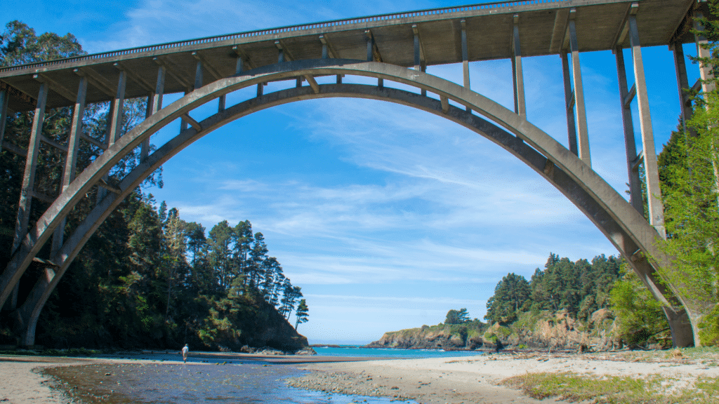 The underside of a large arched bridge over a river that leads to the ocean with cliffs and redwood trees along the side. A man walks in the distance along the river. The sky is blue with wispy clouds and the ocean looks an even brighter blue. This is a California state park called Russian Gulch and it is off the 1 highway.