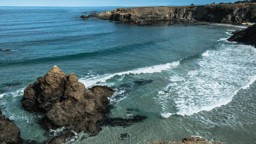 Brown and tan cliffs above a blue green ocean with waves rolling in and crashing closer to the shore along the California Mendocino coast.