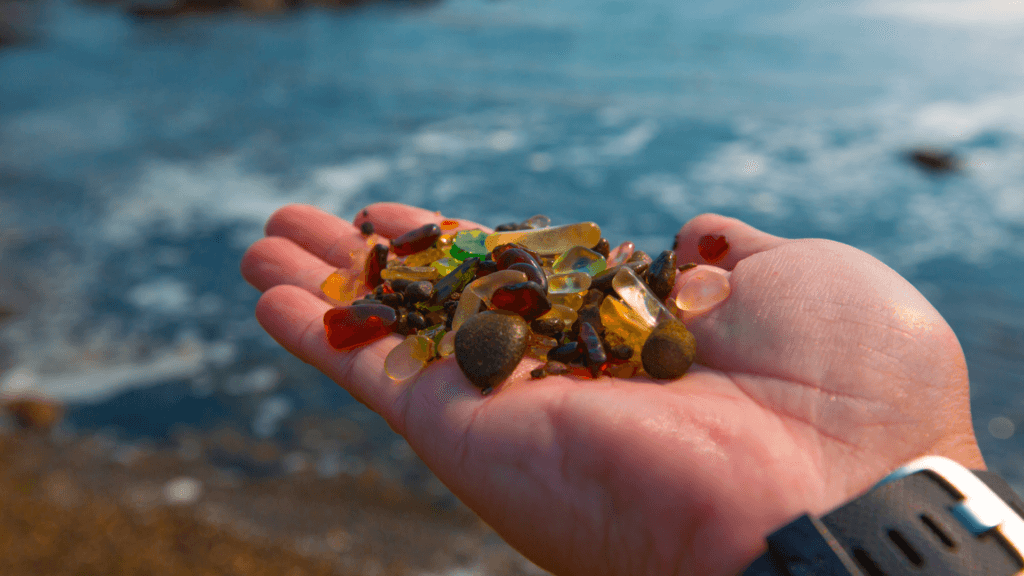 A hand with a black watch band holds a large collection of sea glass above the dazzling blue ocean. This is at MacKerricher state park in California, also known as sea glass beach.