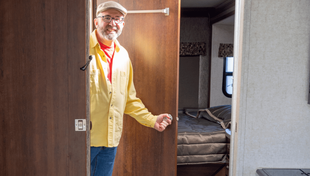 A smiling man holds the doorknob on the bathroom door of an RV while doing an RV walk through.