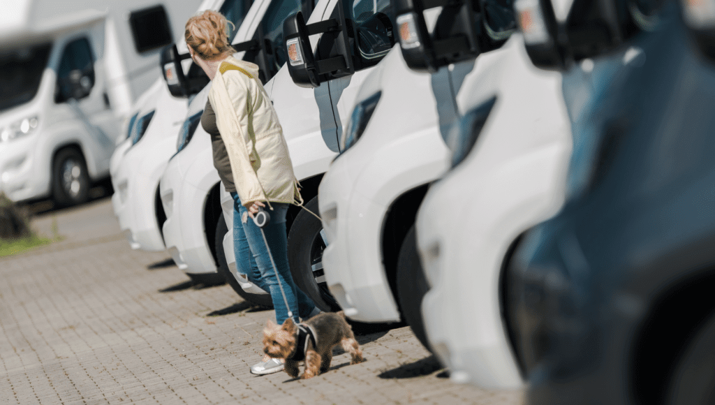 A lady walks with her little dog on the lot of an RV dealership looking at options for buying an RV for the first time