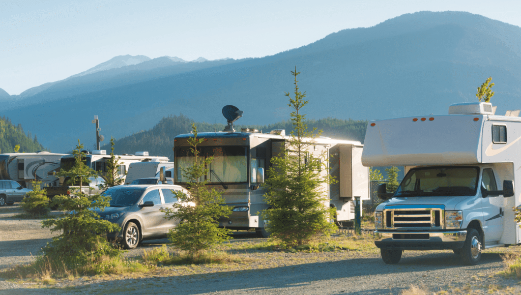At a campground we see different RV types set up including a Class C Motorhome, a Class A Motorhome, a travel trailer and a fifth-wheel.