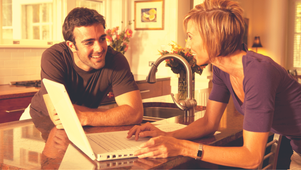 A man an woman are at the kitchen counter looking at a laptop while doing research for buying an RV for the first time.
