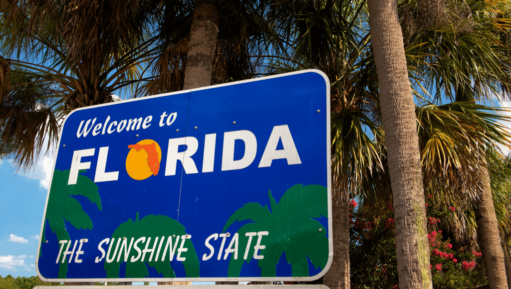 The welcome to Florida sign sits amongst palm trees and pink flowers. The sky is blue with puffy white clouds.