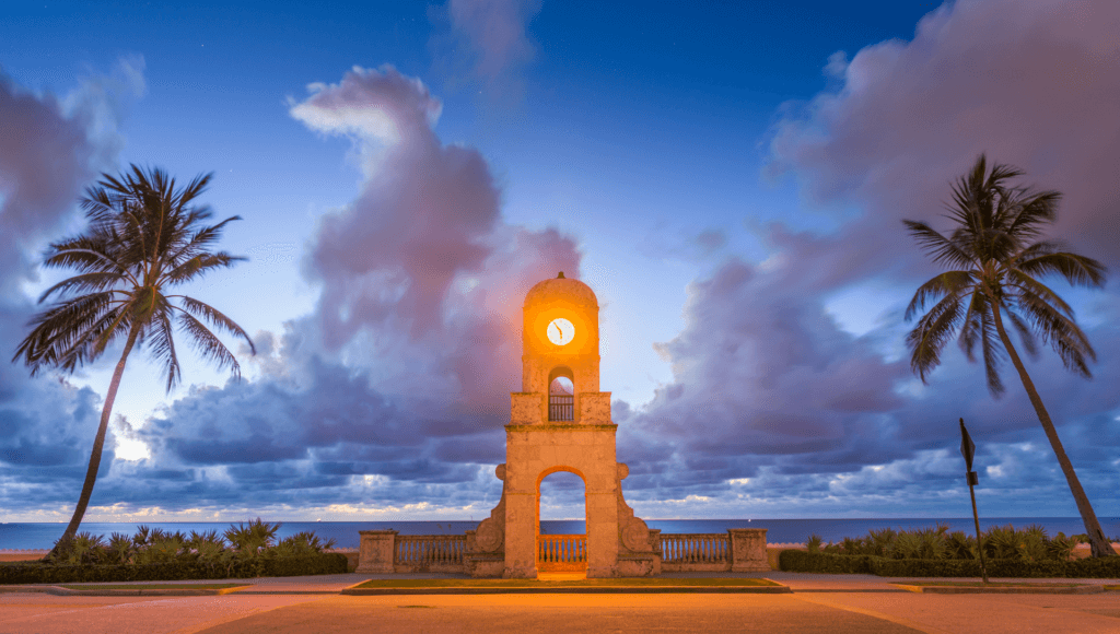 The clock tower in Palm Beach, Florida shines at sunset in front of the ocean. Palm trees are on each side of the tower. The sky is a deep blue with clouds having a purple and pink hue.