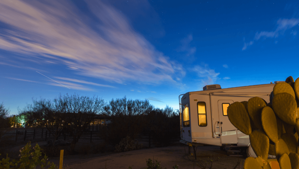An RV is set up at a boondocking location in the desert with deep blue skies during sunset. A large cactus is in the foreground.